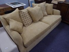 A LOUNGE SUITE COVERED IN OATMEAL COLOURED MOQUETTE, ON LOW WOODEN FEET, COMPRISING A LARGE SEMI-