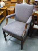 A LARGE UPHOLSTERED ARMCHAIR WITH SCROLL ARMS AND STUD DECORATION, RAISED ON STRAIGHT SUPPORTS