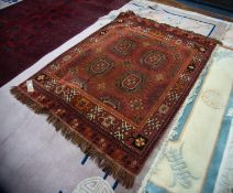 TURKOMAN STYLE MACHINE WOVEN BORDERED RUG with two rows of two large guls and part guls, on a