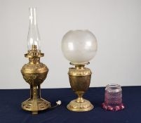 TWO BRASS OIL TABLE LAMPS, one with embossed foot, engraved reservoir and frosted glass shade, 17 ½?