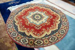 EUROPEAN MACHINE WOVEN CIRCULAR WOOL RUG OF EASTERN DESIGN, with large centre medallion, on a red