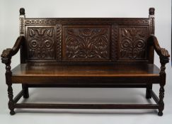 NINETEENTH CENTURY CARVED OAK SETTLE, the three panel back well carved with stylised foliage,