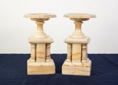 PAIR OF VARIEGATED CREAM ONYX CLOCK SIDE GARNITURES IN TEH FORM OF PEDESTAL DISHES OR VIDE-POCHE,