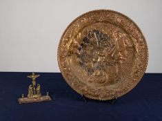 AN INTER-WAR YEARS STAMPED BRASS WALL PLAQUE, and a SMALL BRASS RELIGIOUS DEVOTIONAL ORNAMENT (2)