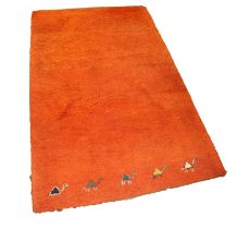 EASTERN MACHINE WOVEN PLAIN ORANGE SMALL CARPET with row of five camels to the bottom edge, 6ft x