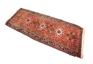EASTERN RUNNER with a row of seven alternating medallions, on a wine red field with scattered