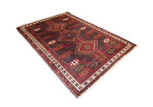 EASTERN CARPET with three diamond pole medallions, on a tile pattern field, the colour predominantly