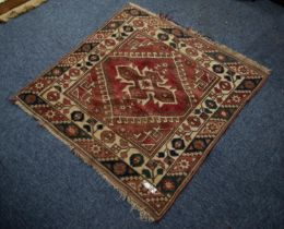 SMALL EASTERN RUG, the red field filled with a centre medallion within a diamond shaped latch hook