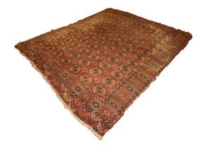 OLD TURKOMAN BOKHARA CARPET with seven rows of twelve octagonal guls on a wine red field, broad