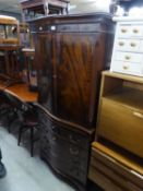 A FIGURED MAHOGANY COCKTAIL CABINET, WITH SERPENTINE FRONT, TWO DOORS OVER A SLIDE, DRAWER AND