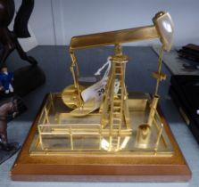 A CLOCKWORK BRASS MODEL OF AN OIL WELL PUMP, ON OBLONG BASE