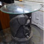 A LAMP TABLE, WITH CIRCULAR GLASS TOP, ON BLACK FIBREGLASS DRUM SHAPED BASE, EMBOSSED IN HIGH RELIEF