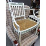 AN ANTIQUE WHITE PAINTED AND DECORATED TUB SHAPED OPEN ARMCHAIR, WITH RAIL BACK, CANE PANEL SEAT, ON