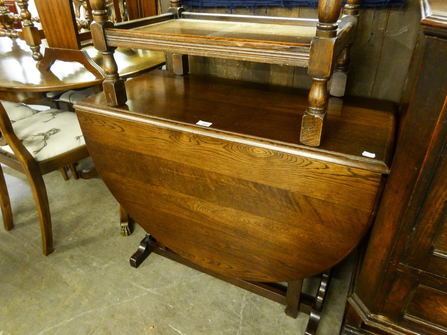 AN OAK OVAL GATE LEG DINING TABLE, ON TWO TRESTLE SUPPORTS WITH SLEDGE FEET, THE PLAIN GATE LEGS