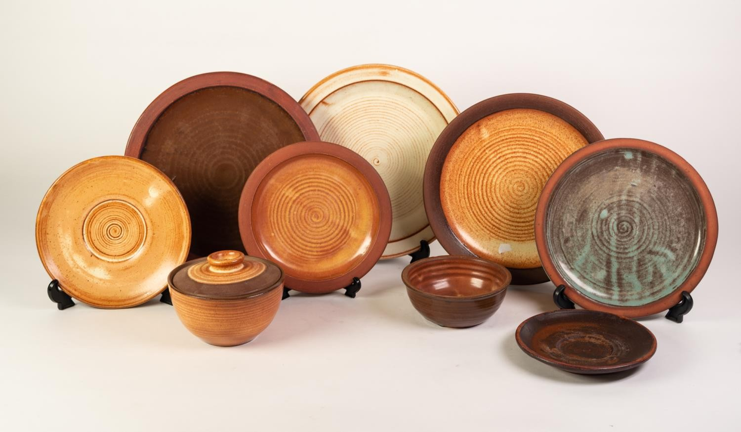 TWENTY ONE DAVID LEACH STYLE POTTERY PLATES IN FOUR SIZES, each with unglazed rims and slightly