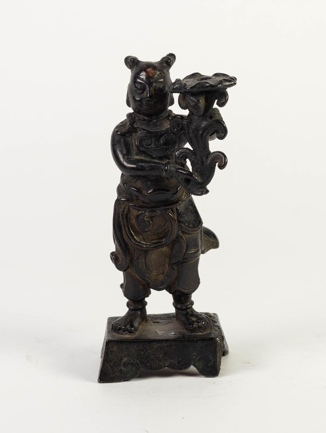 ANTIQUE CHINESE PATINATED BRONZE FIGURAL CANDLESTICK, modelled as a robed figure holding a floral