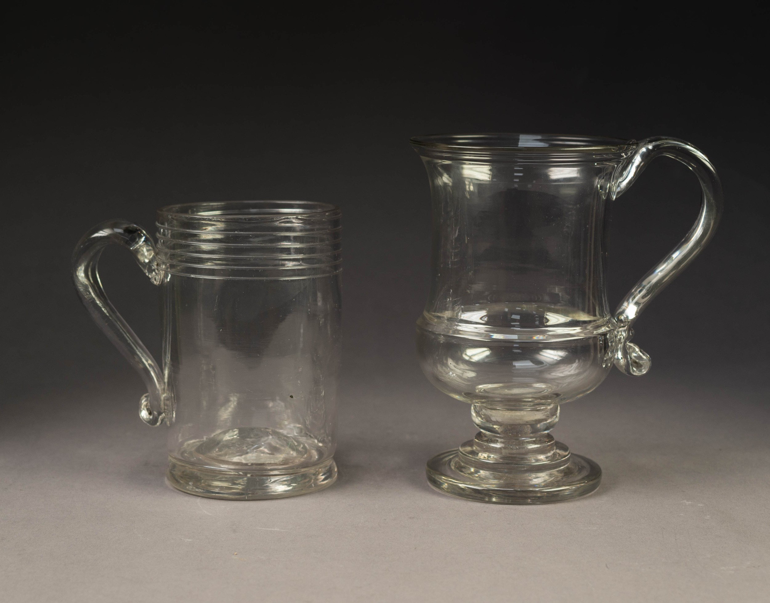 TWO ANTIQUE GLASS TANKARDS WITH LOOSE GEORGIAN COINS IN THE BASES, 5 ¼? (13.3cm) high, the other