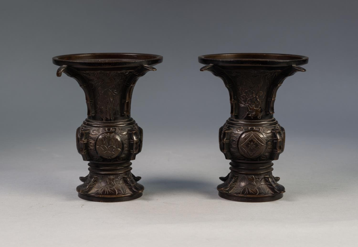 PAIR OF JAPANESE LATE MEIJI PERIOD BRONZE VASES, each of flared form, engraved with panels