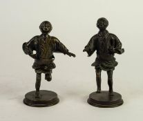 PAIR OF ORIENTAL BRONZE FIGURES, each modelled with foot raised, on a circular base, unmarked,