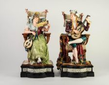 PAIR OF LATE NINETEENTH CENTURY CONTINENTAL FAIENCE FIGURE SEATED IN CHAIRS, he with guitar and