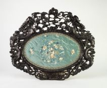 NINETEENTH CENTURY CHINESE HAND WORKED SILK OVAL PANEL IN ORNATELY CARVED HARDWOOD FRAME, the