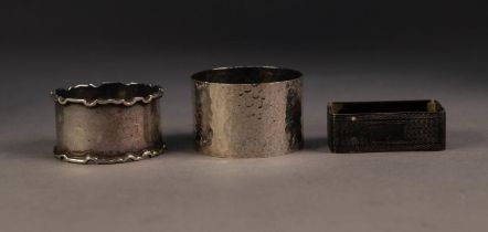 THREE SILVER NAPKIN RINGS, including an OBLONG, ENGINE TURNED EXAMPLE and another, PLANISHED, by