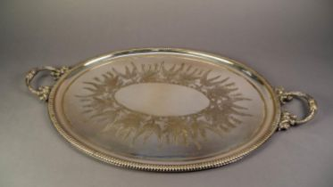 LATE VICTORIAN ELECTROPLATED OVAL GADROON BORDERED TWO HANDLED TEA TRAY, the centre decorated with
