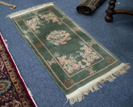 """A WASHED CHINESE OBLONG RUG, with dragon medallion and spandrels on a moss green field, 4'6"""" x 2'4"""""""