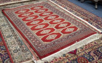 PAKISTAN BOKHARA RUG, with two rows of primary guls on a crimson field divided by three rows of