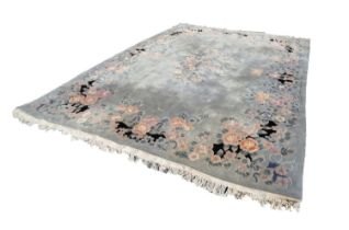 LARGE WASHED CHINESE CARPET, with a plain pale blue/grey field, embossed oval floral centre