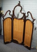 EARLY TWENTIETH CENTURY CARVED MAHOGANY THREE FOLD SCREEN, each section with a shaped bevel edge