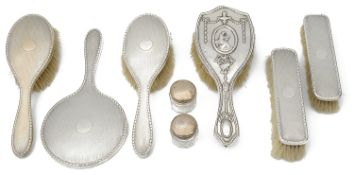 A George V engine turned silver backed five piece dressing table set; others