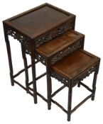 A late 19th century Chinese hardwood nest of three occasional tables
