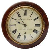 An early 20th century small oak cased circular drop dial wall clock