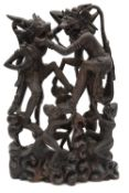 A 20th century Balinese hardwood carving depicting monkeys engaged in battle,