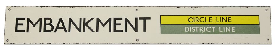 A London Underground enamel station sign for Embankment,with black lettering on a white ground and a