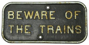 A cast iron notice displaying 'BEWARE OF THE TRAINS'