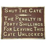 A vintage cast iron sign displaying 'SHUT THE GATE'