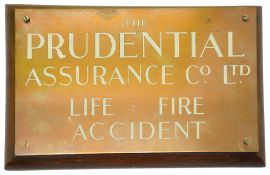 A Prudential Assurance Company copper sign mounted on wooden board,