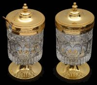 A pair of continental gilt metal and moulded crystal preserve pots and covers, (2)