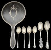 A George V silver mounted tortoiseshell hand mirror and various silver spoons.