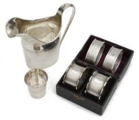 An Edwardian silver helmet shaped cream jug, a cased pair of Vict. napkin rings and other items