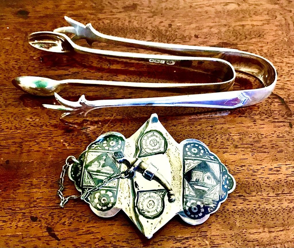 SILVER COLOURED THAI BUCKLE AND TWO PAIRS OF SILVER SUGAR TONGS