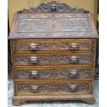 Late 19th / early 20th century heavily carved fronted oak fall front writing bureau, with fitted