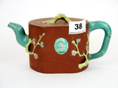 A Chinese hand painted and relief decorated terracotta teapot. Condition: A/F.