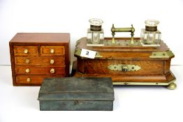 A Victorian brass mounted oak desk stand with cut glass bottles, together with a French travelling