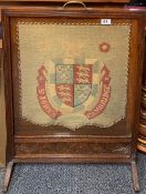 A 1920's oak fire screen inset with a tapestry panel for St. John's College in Cambridge, H. 77cm.