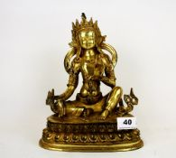 A Tibetan gilt bronze figure of a seated Buddha, H. 25cm. Holding a sacred bell in his left hand and