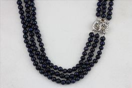 A triple row blue /black cultured pearl necklace on a stone set white metal clasp, L. 44cm, together