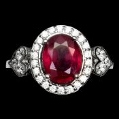A 925 silver cluster ring set with an oval cut ruby surrounded by white stones, (O).